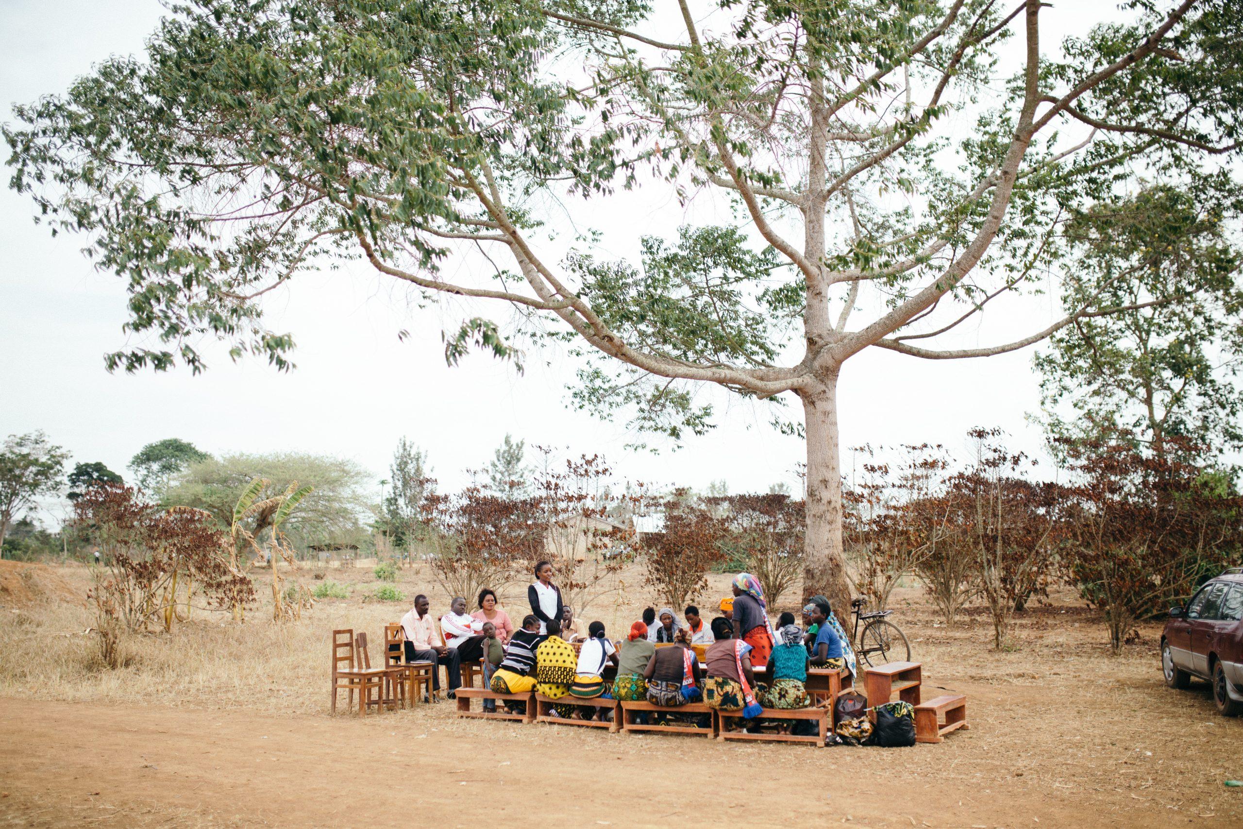 Tansanische Frauen in Bunten Gewändern sitzen unter einem Baum an einem Tisch zu einem Treffen zusammen