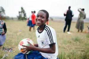 Junge sitzt mit Fußball im Gras
